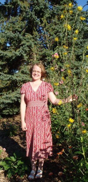 A woman standing next to a very tall sunflower