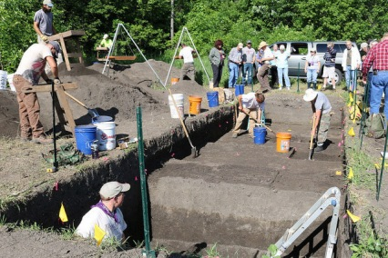 wide shot of the excavation site, with archaeologists digging and others sifting