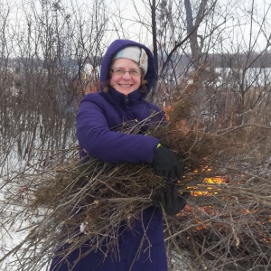 A woman holding a pile of brush in front of a brush pile that's on fire