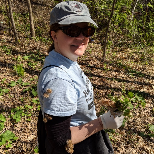 A woman smiling at the camera while holding garlic mustard, with burrs stuck on her shirt.