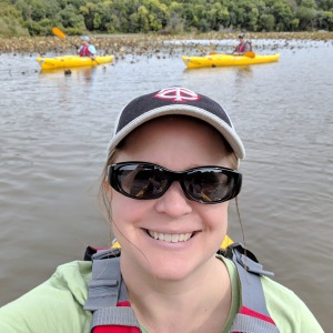 Selfie taken from a kayak, with two kayakers in the background.